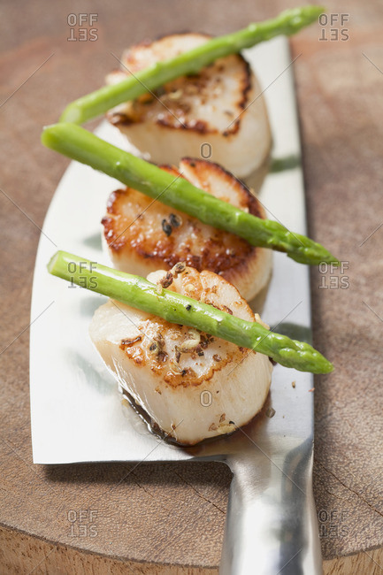 Fried scallops with green asparagus on cleaver