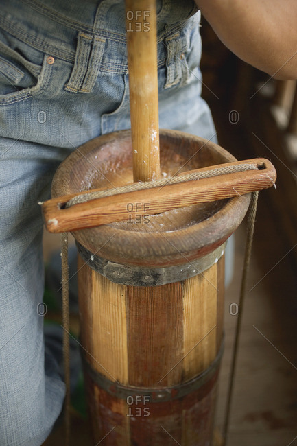 Person churning butter in a butter churn