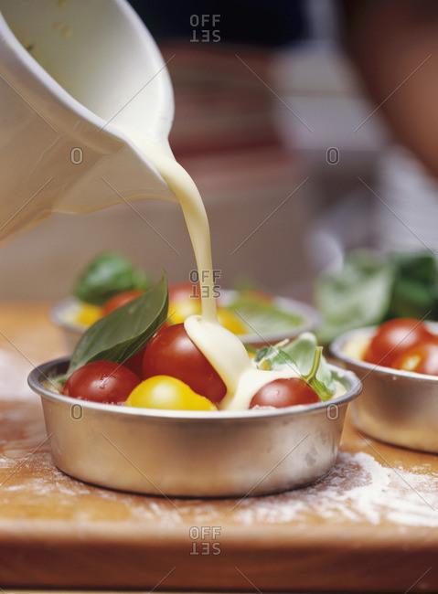 Pouring egg and milk mixture into individual tomato quiche