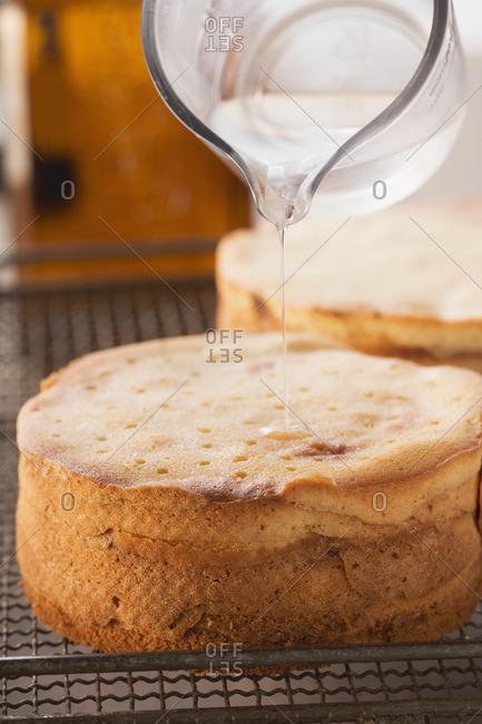 Baumkuchen (German layer cake) being prepared: drizzling with orange liqueur