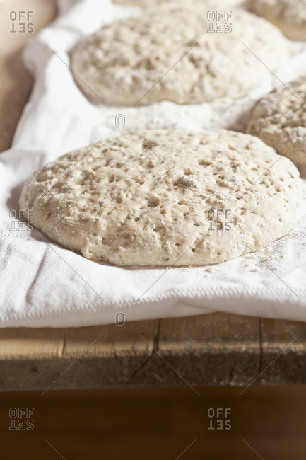 Unbaked loaves of bread on linen cloth