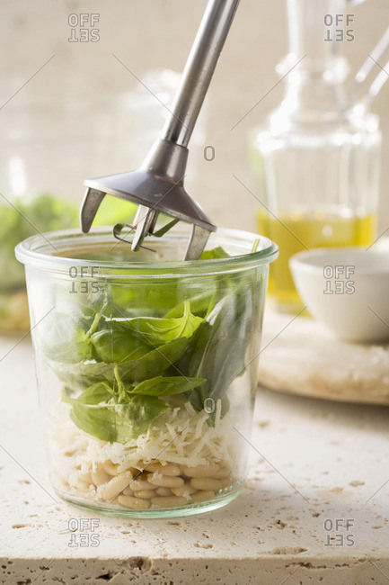 Basil, Parmesan and pine nuts being mixed with a hand mixer