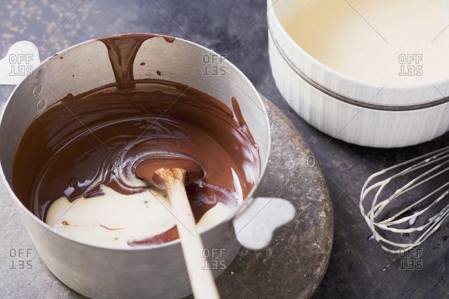 Melted chocolate being stirred into a milk-cream-egg yolk mixture