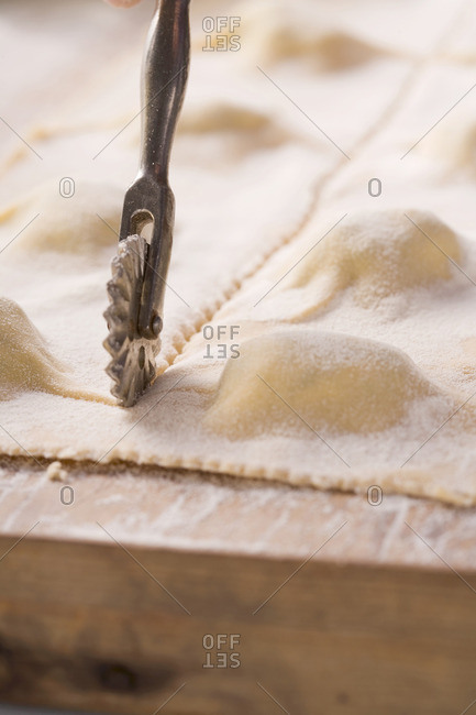 Herb ravioli being cut with a pastry cutter