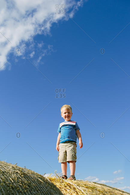 Toddler boy standing on top of a hay bale