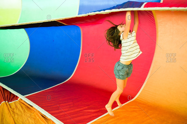 Little girl playing inside a colorful rainbow parachute