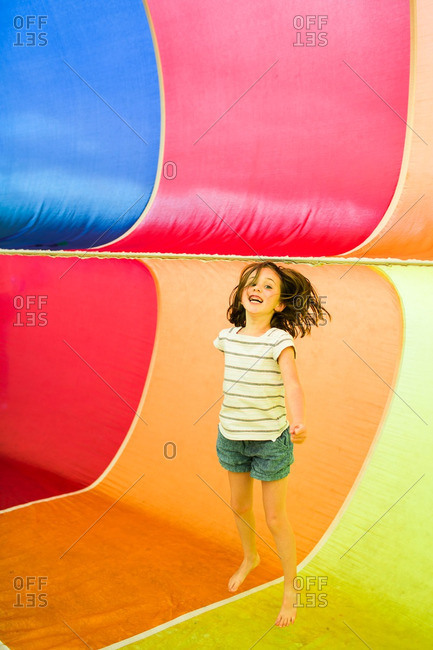 Little girl jumping inside a colorful rainbow parachute