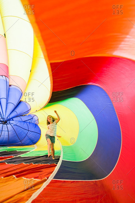 Girl playing in an inflated rainbow parachute