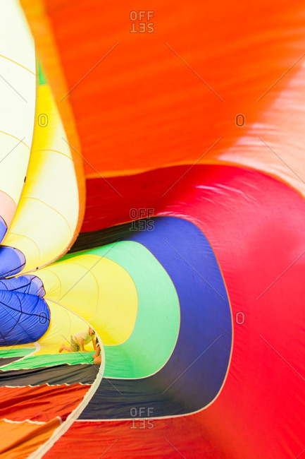 Children playing inside an inflatable rainbow parachute