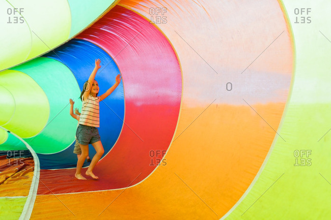 Boy and girl running around a colorful rainbow parachute