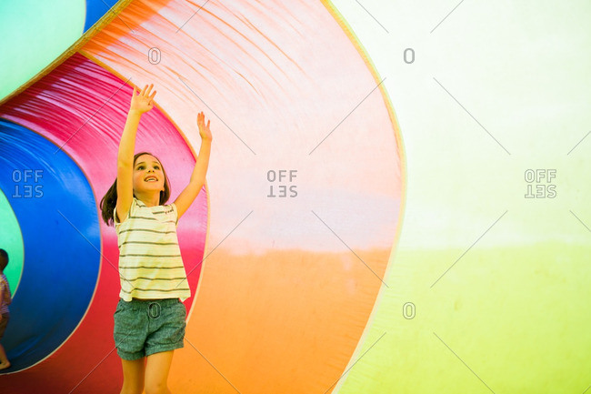 Girl playing inside an inflatable rainbow parachute