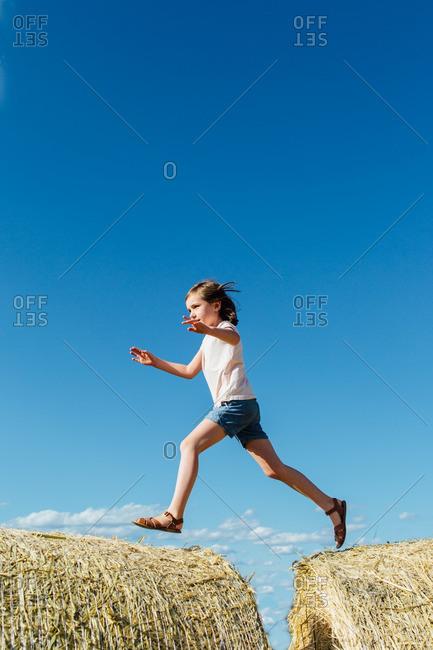 Little girl walking across the top of two hay bales in a field