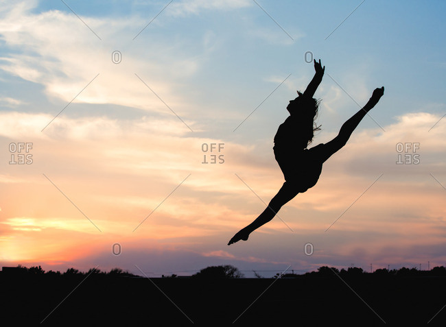 Silhouette of a woman leaping through the air