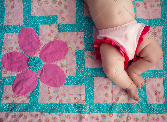 Baby lying down on a colorful quilt