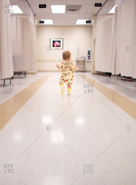 Toddler walking down an aisle in a hospital