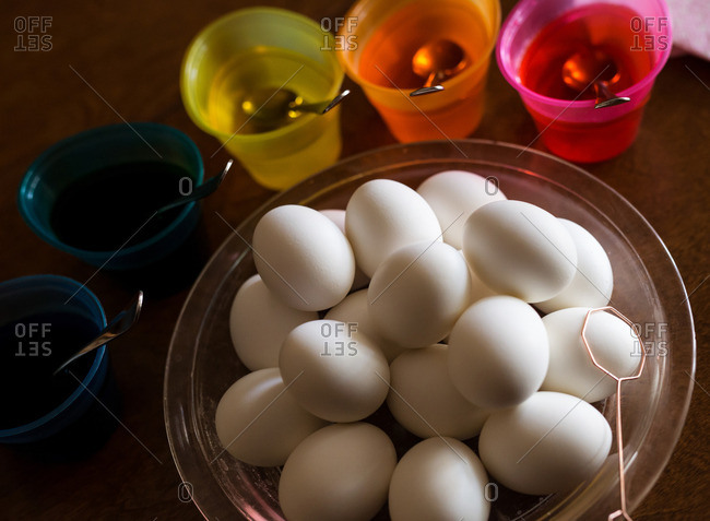 Eggs in a bowl next to cups filled with colored dye