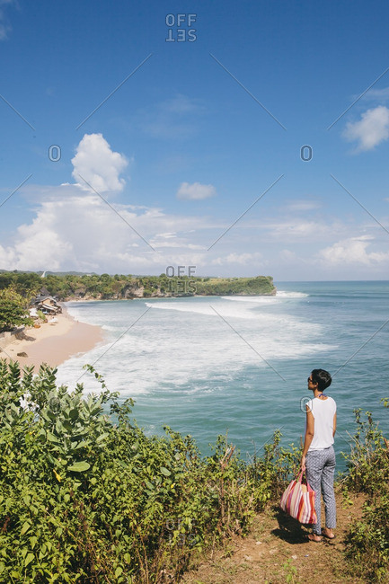 Bali, Indonesia - May 13, 2014: Woman with bag looking at beach from viewpoint