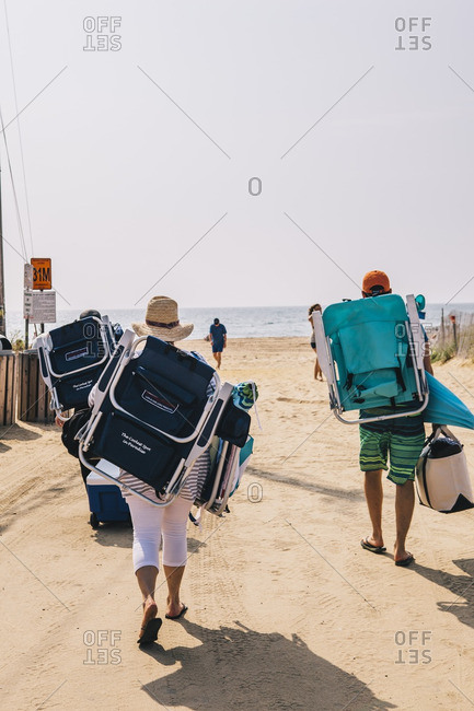 East Hampton, New York - September 4, 2015: Two people walking to beach with coolers and beach chairs