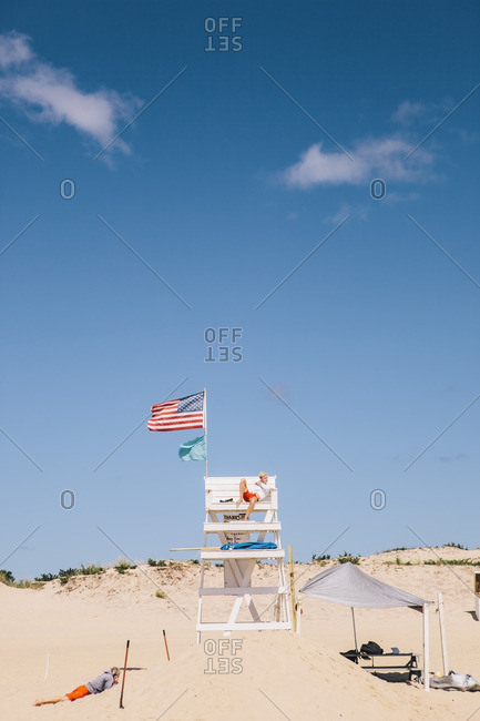 East Hampton, New York - September 5, 2015: Lifeguard in elevated chair watches over beach