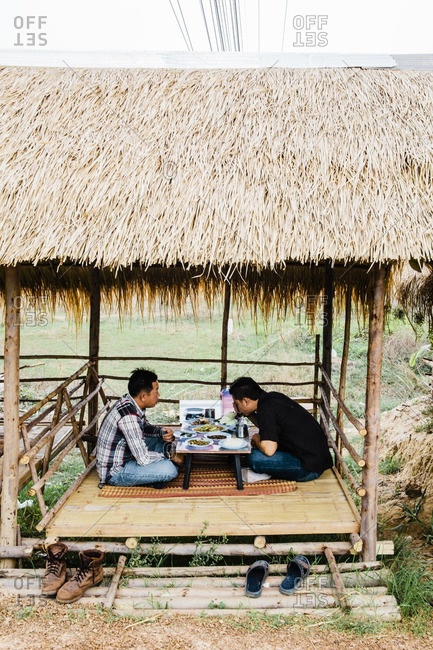Isan, Thailand - March 23, 2015: Two men at roadside food stall eating Isaan food of papaya salad and grilled chicken