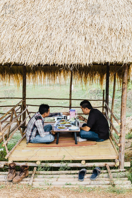 Isan, Thailand - March 23, 2015: Two men at roadside food stall selling Isaan food of Som Tam and Gai Yang