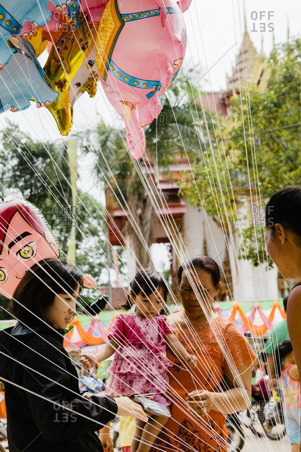 Isan, Thailand - March 23, 2015: Child and mother choosing balloon at fair