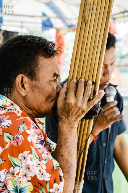 Isan, Thailand - March 23, 2015: Man singing traditional songs accompanied by bamboo pipe mouth organ