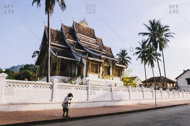 Man sweeping sidewalk next to Buddhist temple