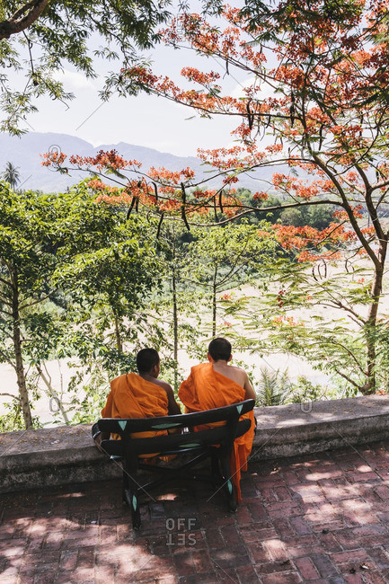 Monks sitting on bench overlooking the Nam Khan river