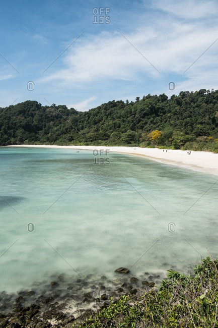 White sand beach surrounding clear water of bay at isolated Kyun Phi Lar Island