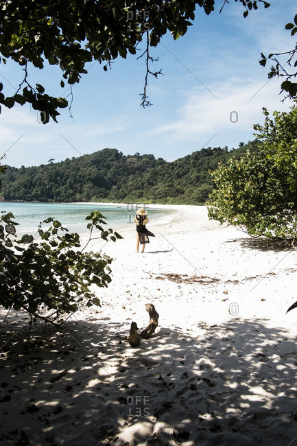 Woman walking on white sand beach surrounding clear water of bay at isolated Kyun Phi Lar Island