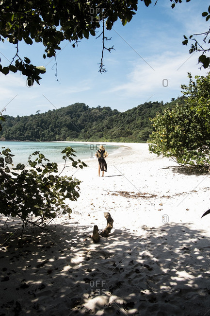 Woman walking on white sand beach looking out at clear water of bay at isolated Kyun Phi Lar Island