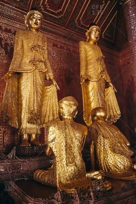 Two Gold leaf covered wooden Buddha statues and kneeling attendants