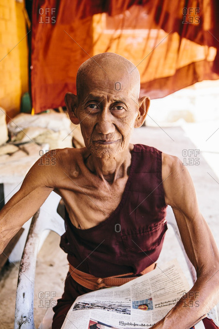 Yangon, Myanmar - March 12, 2015: Elderly monk in maroon robes at Kyaukhtatgyi Pagoda