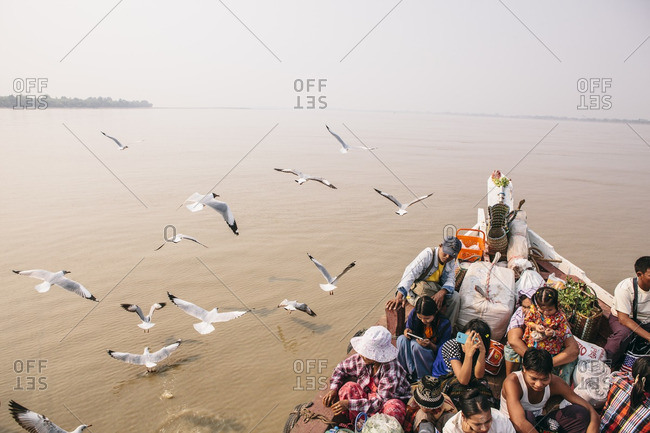Seagulls following a river ferry full of passengers and belongings