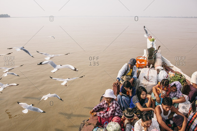 Myanmar - March 18, 2015: Seagulls following a river ferry full of passengers and belongings