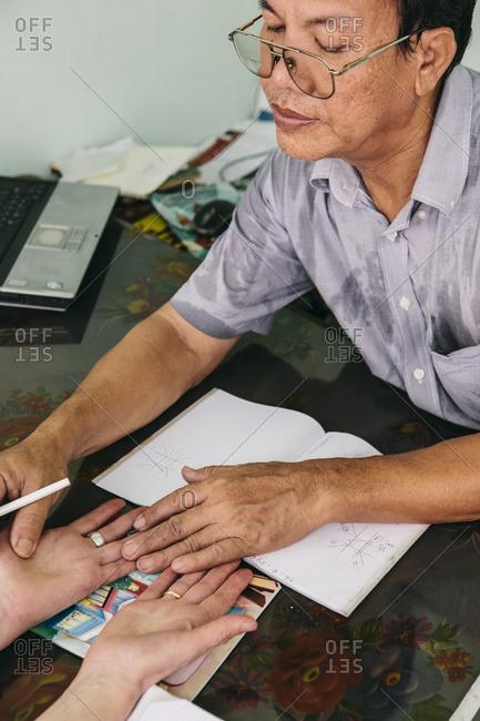Yangon, Myanmar - March 20, 2015: Fortune teller reading palms