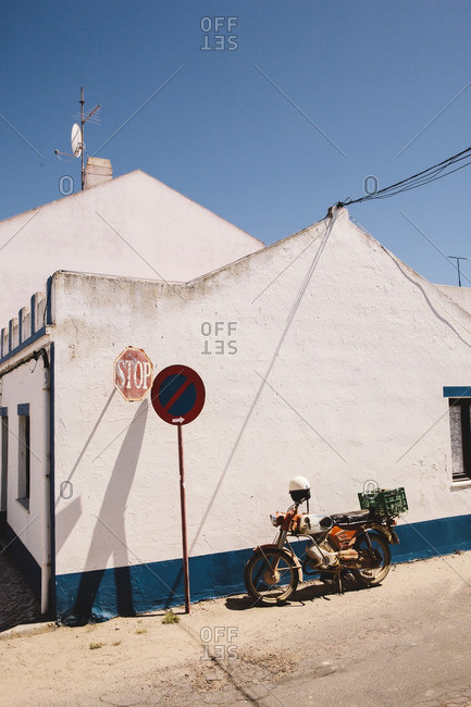 Pego Beach, Portugal - June 30, 2014: Old motorcycle parked next to blue and white painted houses