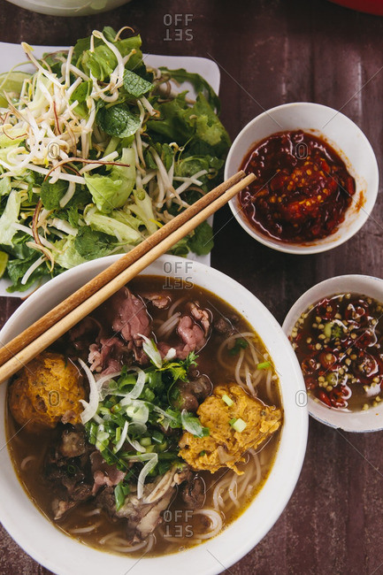 A bowl of Hue style beef noodle soup with fresh herbs