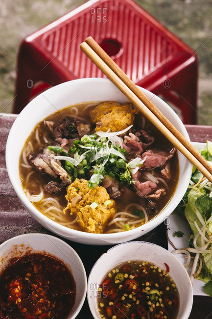 A bowl of Bun Bo Hue with fresh herbs on table with red stool