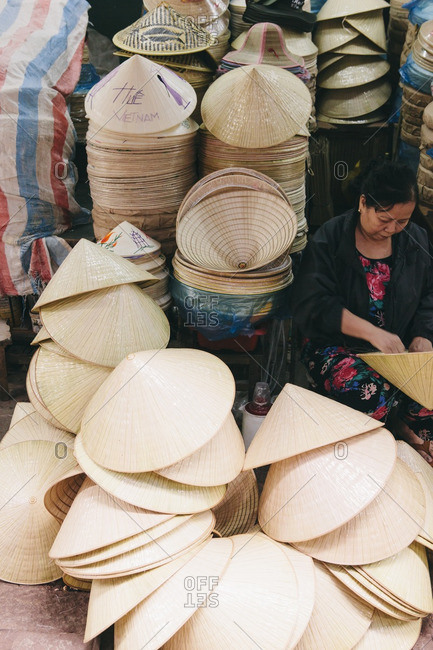 Hue, Vietnam - March 9, 2014: Woman sitting among pile of Vietnamese conical hats