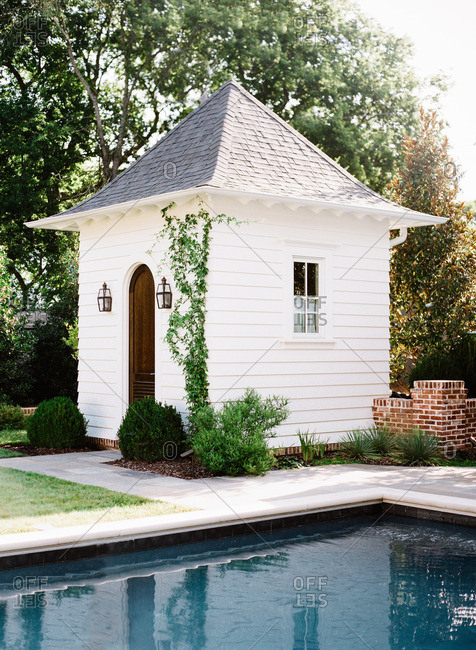 Small white pool house with ivy next to a swimming pool