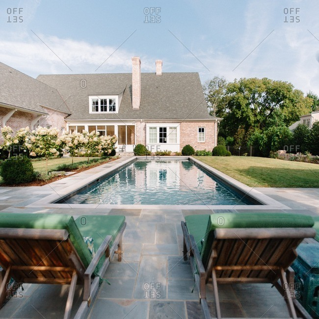Outdoor swimming pool and patio with lounge chairs