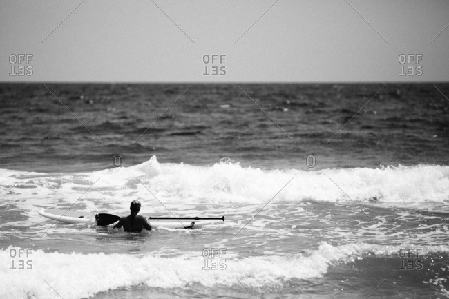 Stand up paddle boarder anticipating a wave