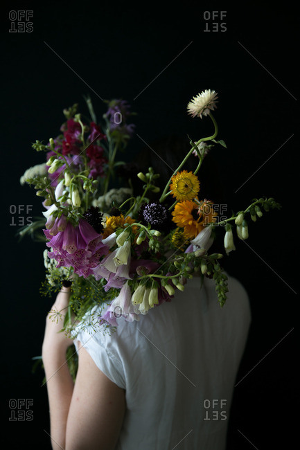 Back view of a person holding a bouquet of flowers