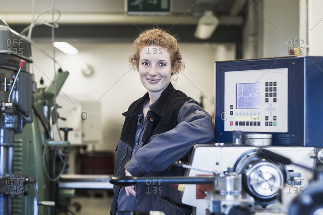Portrait of a young female engineer standing in an industrial plant, Freiburg im Breisgau, Baden-Wurttemberg, Germany