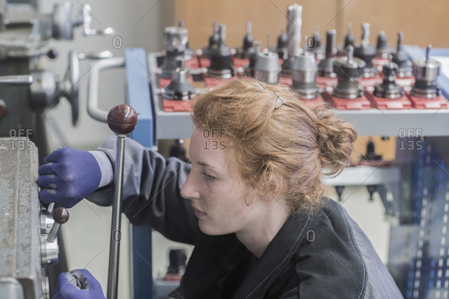 Young female engineer operating lever in an industrial plant, Freiburg im Breisgau, Baden-Wurttemberg, Germany