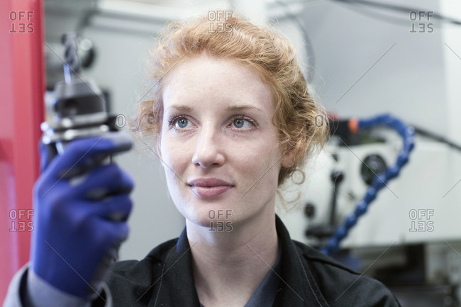 Young female engineer working with drill bit in an industrial plant, Freiburg im Breisgau, Baden-Wurttemberg, Germany
