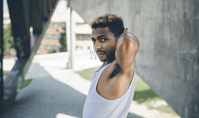 Portrait of young man doing stretching exercises