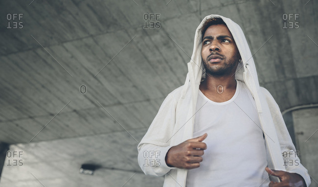 Serious young man wearing hooded jacket looking at distance